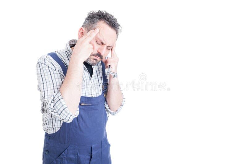 Mecânico novo forçado que olha esgotado e que sofre do hea fotografia de stock royalty free