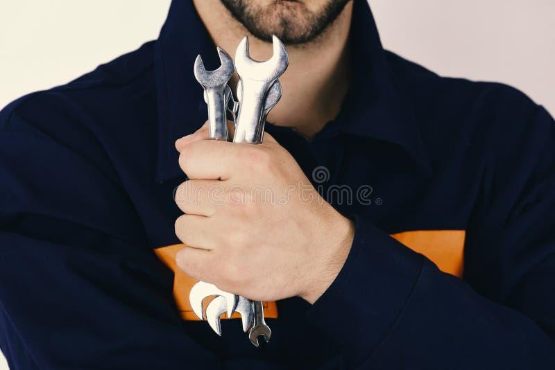Mecânico ou encanador com equipamento metálico da chave inglesa à disposição Instrumentos da chave inglesa para fixar ou apertar  imagens de stock royalty free
