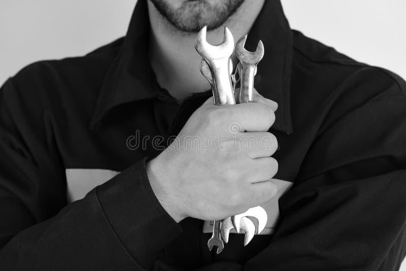 Mecânico ou encanador com equipamento metálico da chave inglesa à disposição Instrumentos da chave inglesa para fixar ou apertar  imagem de stock