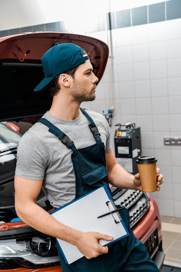 mecânico pensativo com o café a ir e o bloco de notas que inclina-se no carro com capuz aberto imagem de stock
