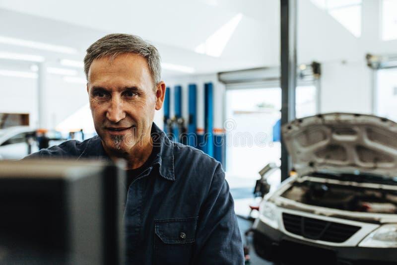 Mecânico que faz o diagnóstico do carro no computador fotografia de stock