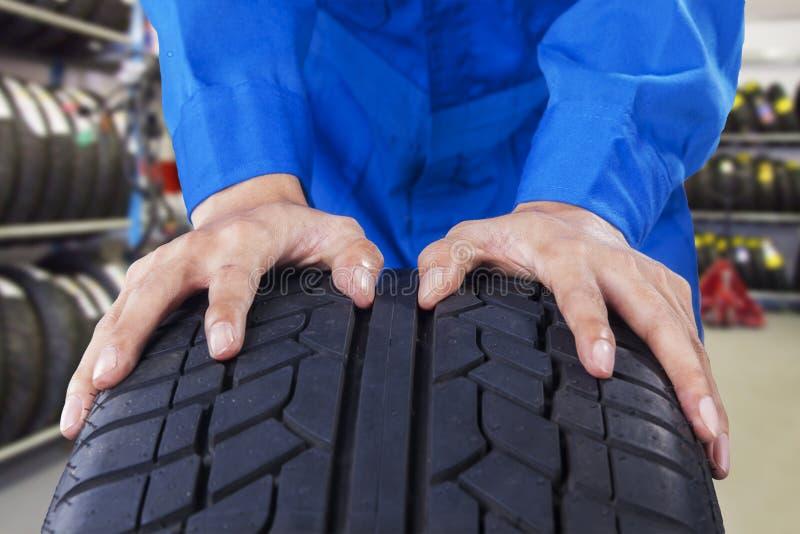 Mecânico que guarda um pneu na loja do veículo fotos de stock