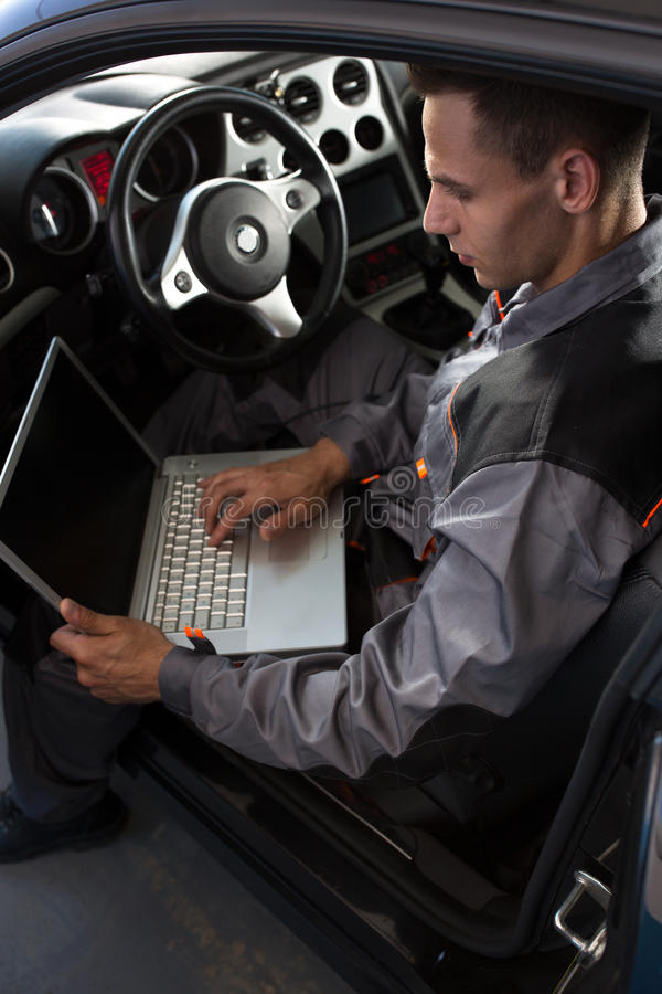 Mecânico que olha o computador diagnóstico fotos de stock royalty free
