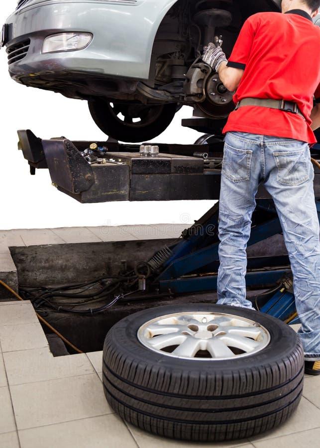 Mecânico que presta serviços de manutenção a um carro com o pneumático na terra imagem de stock royalty free