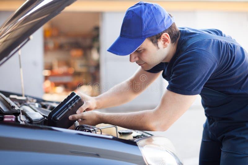 Mecânico que presta serviços de manutenção a um motor de automóveis foto de stock
