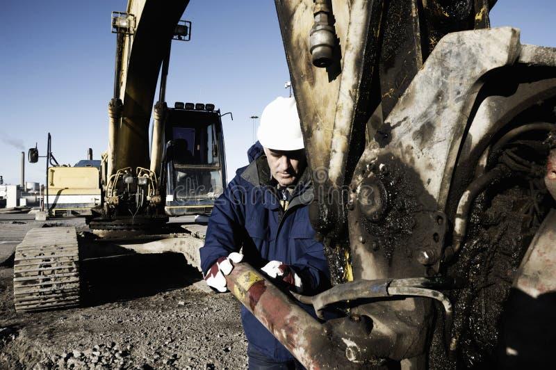 Mecânico que repara a hidráulica em uma escavadora imagem de stock