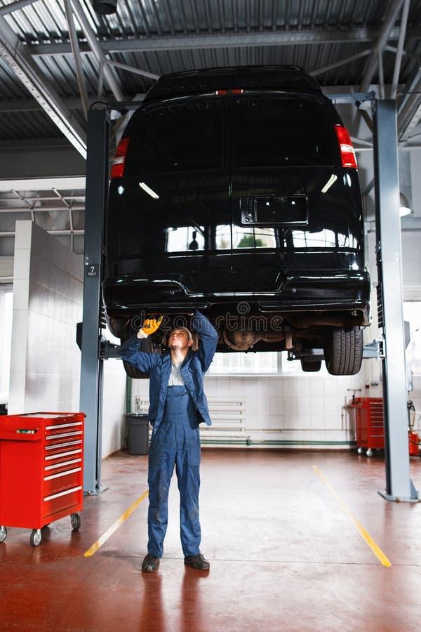 Mecânico que trabalha com sistema de suspensão do carro foto de stock