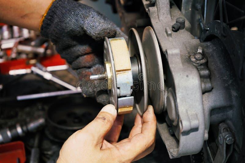 Mecânico que trabalha instalando o sistema da embreagem na motocicleta velha do 'trotinette' na garagem da motocicleta Substituiç imagens de stock