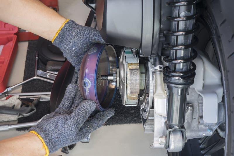 Mecânico que trabalha na garagem, limpeza e reparando o sistema traseiro da embreagem de motocicleta grande do 'trotinette', de r fotografia de stock royalty free