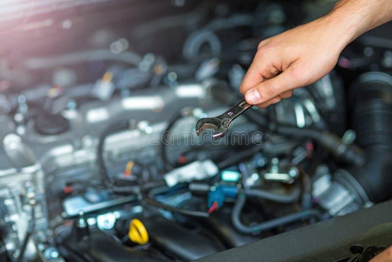 Mecânico que trabalha no motor de automóveis na loja de reparação de automóveis imagens de stock