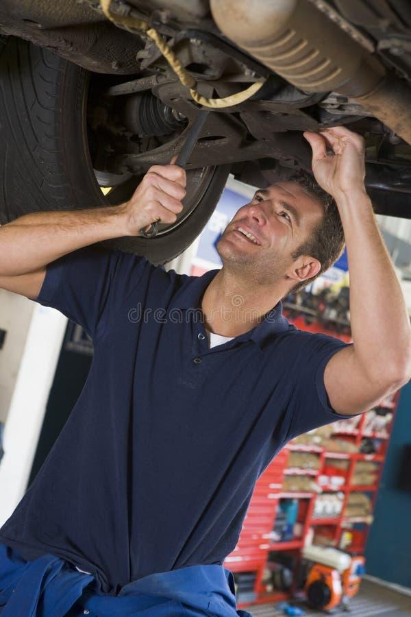 Mecânico que trabalha sob o carro imagens de stock royalty free