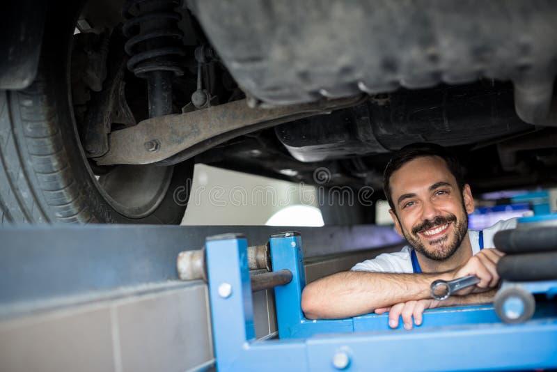 Mecânico que trabalha sob o sorriso do carro fotografia de stock royalty free