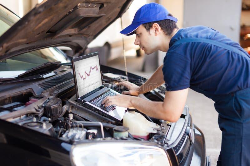 Mecânico que usa um laptop para verificar um motor de automóveis foto de stock royalty free