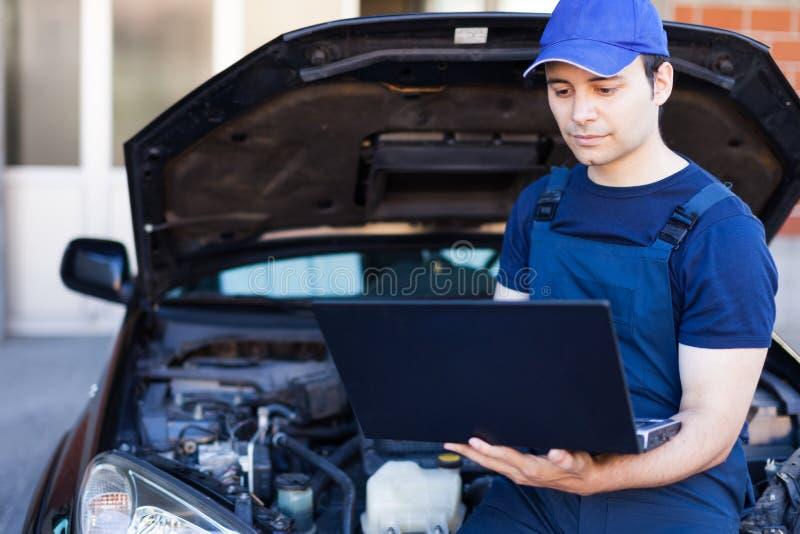 Mecânico que usa um laptop para verificar um motor de automóveis imagens de stock