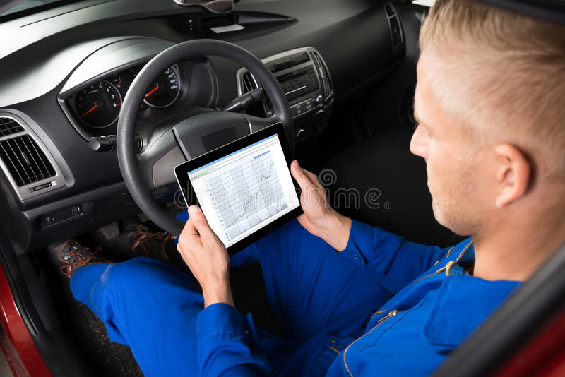 Mecânico Sitting In Car que olha a tabuleta de Digitas fotografia de stock royalty free