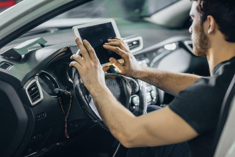 Mecânico Sitting In Car que olha a tabuleta de Digitas na garagem imagem de stock royalty free