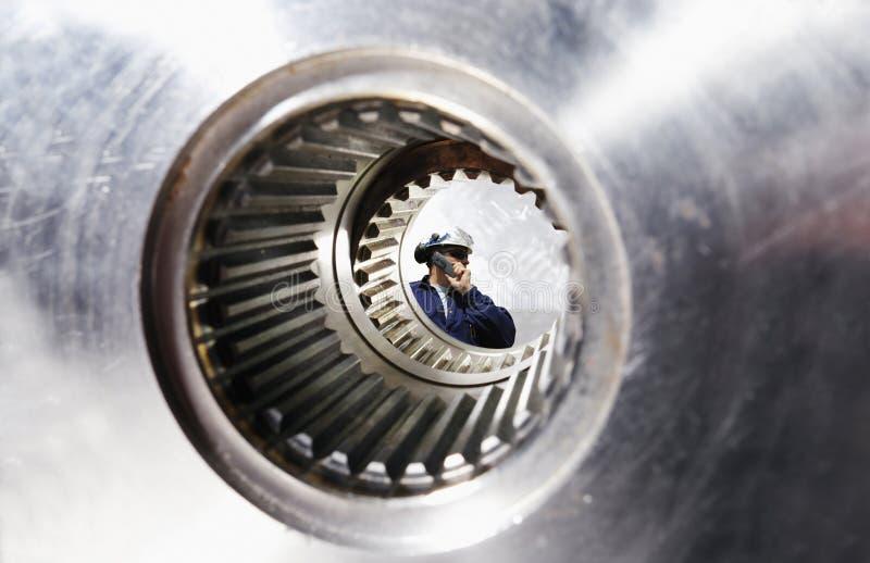 Mecânico, trabalhador visto através de um eixo gigante da engrenagem imagens de stock