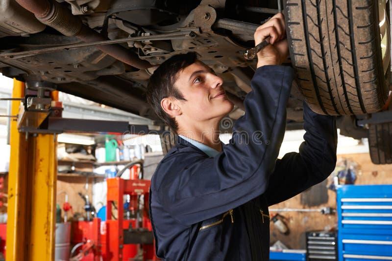 Mecânico Working Under Car do aprendiz foto de stock royalty free