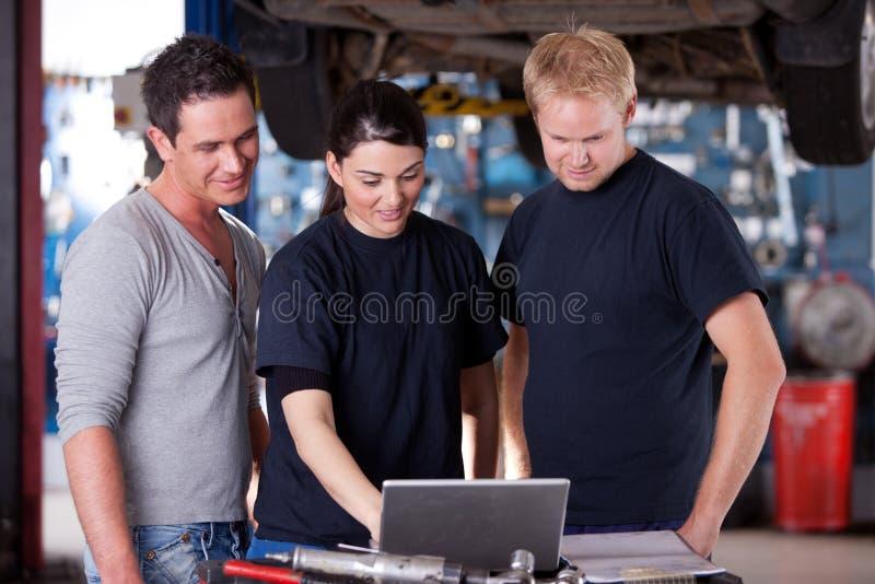 Mecânicos com portátil imagens de stock royalty free