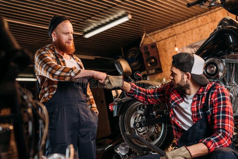 mecânicos consideráveis que fazem o punho do bro na motocicleta imagem de stock