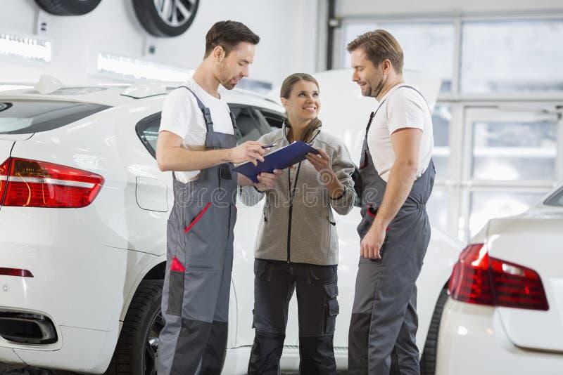 Mecânicos de automóvel que discutem sobre a prancheta na oficina de reparações do carro fotos de stock royalty free