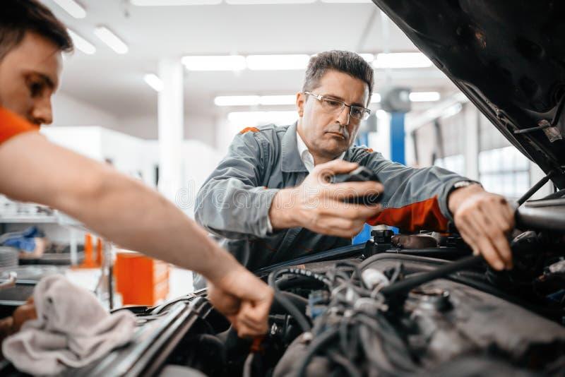 Mecânicos de carro que trabalham e que mantêm o carro foto de stock royalty free