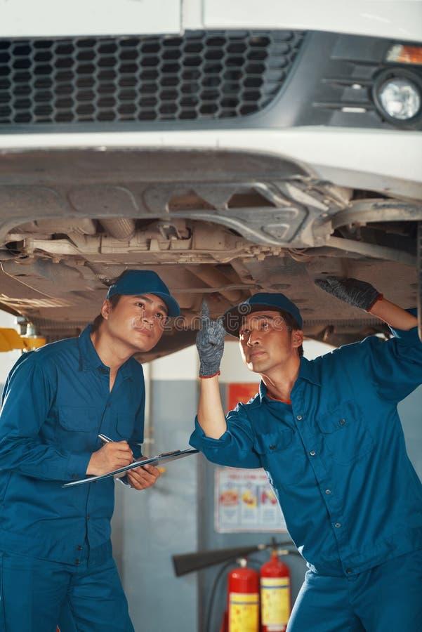 Mecânicos que inspecionam o fundo do carro fotos de stock royalty free