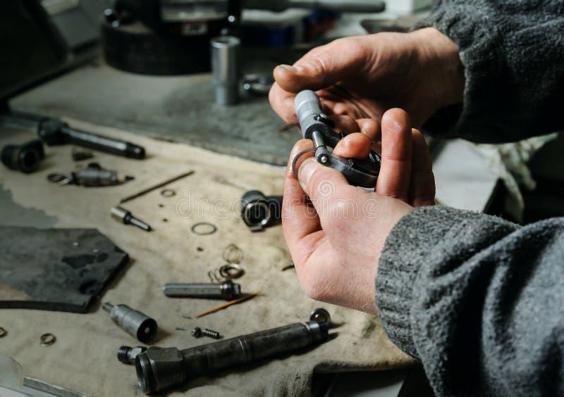Mecânicos uma reparação de um injetor diesel imagem de stock
