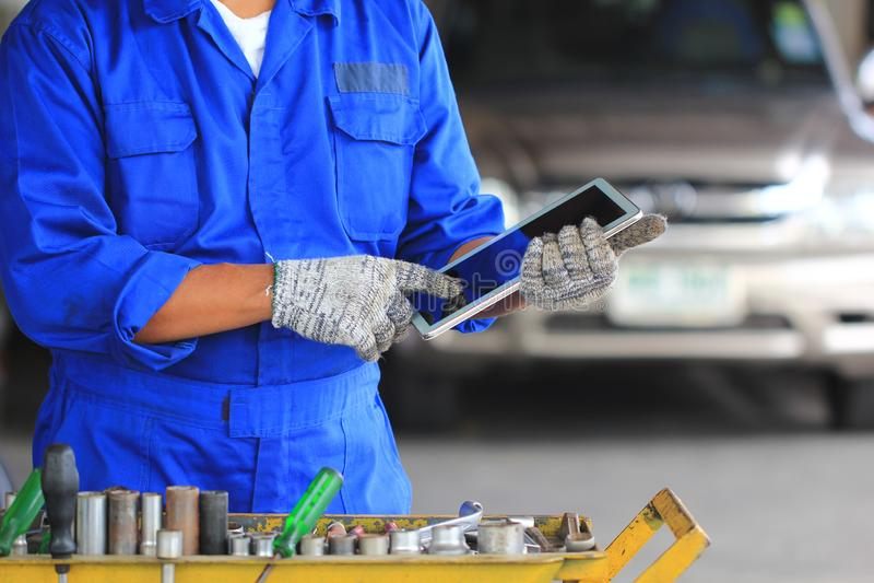 Mec?nico de carro que guarda a tabuleta digital no servi?o de repara??o de autom?veis imagens de stock