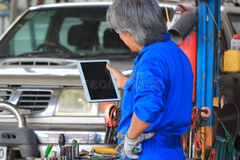 Mec?nico de carro que guarda a tabuleta digital no servi?o de repara??o de autom?veis imagens de stock royalty free