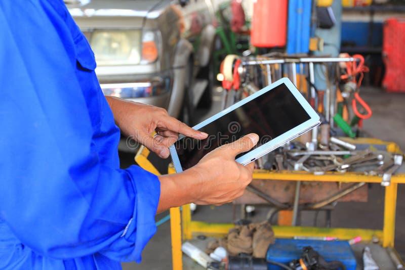 Mec?nico de carro que guarda a tabuleta digital no servi?o de repara??o de autom?veis fotografia de stock