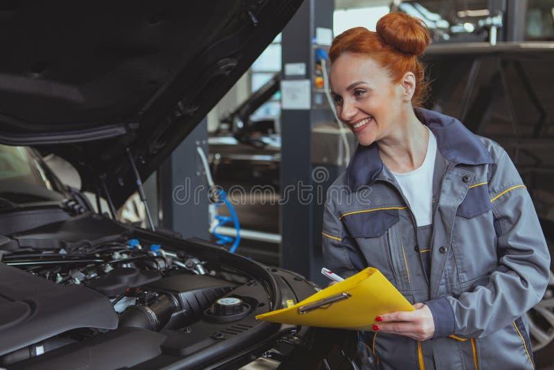 Mec?nico de sexo femenino que trabaja en la gasolinera del coche imagenes de archivo
