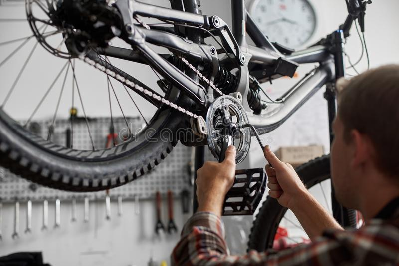 Mec?nico de sexo masculino que trabaja en el taller de reparaciones de la bicicleta usando las herramientas imágenes de archivo libres de regalías