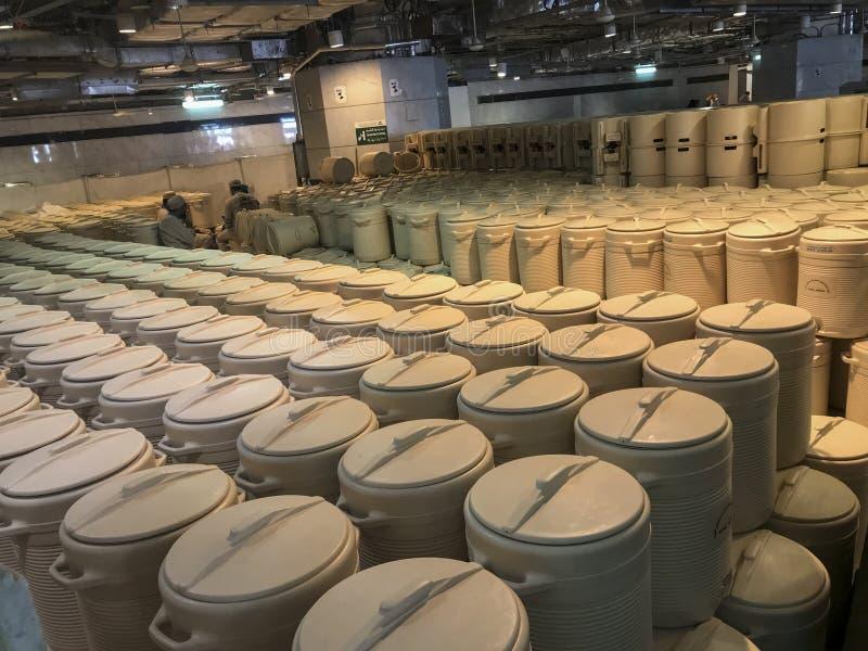 MECA, ARÁBIA SAUDITA - 1º DE JUNHO DE 2019: Os trabalhadores descansam entre centenas de cilindros da água do zamzam dentro da me fotografia de stock royalty free