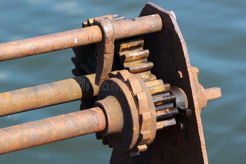 Mecanismo da catraca e do retentor do guincho oxidado velho em um cais fotografia de stock