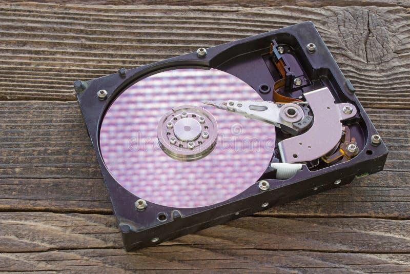 Mecanismo interno do disco rígido no fundo de madeira imagem de stock