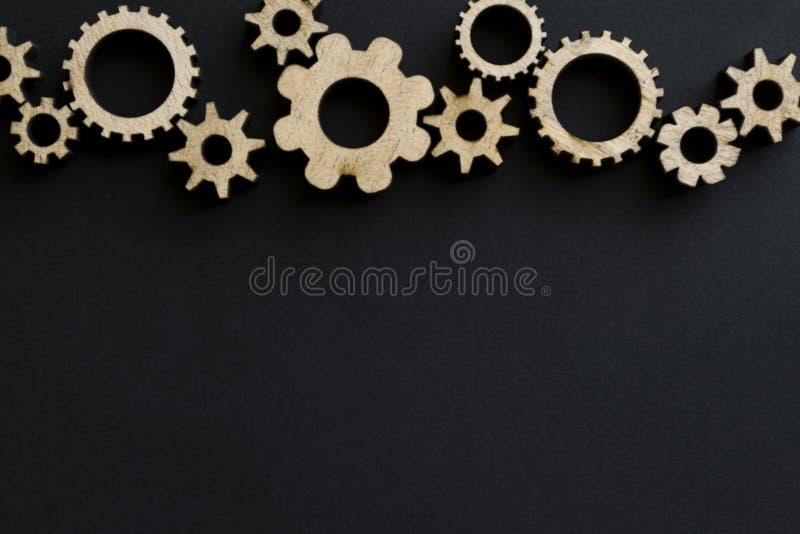 Mecanismos de madeira em um fundo preto Placa de giz preta foto de stock royalty free