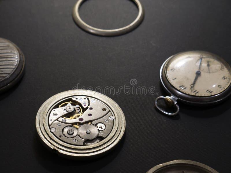 Mecanismos dos relógios e das suas partes em um fundo preto imagem de stock