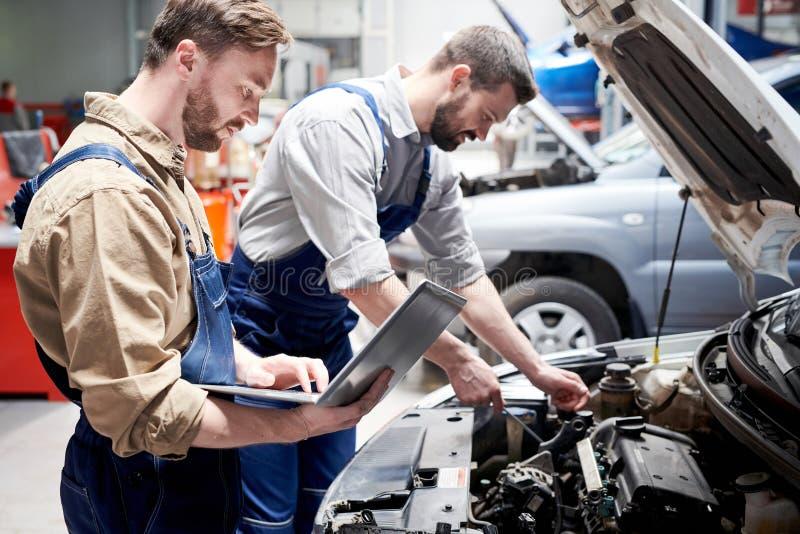 Meccanici che lavorano nel servizio dell'automobile immagine stock libera da diritti