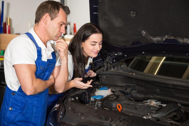 Meccanici in garage che ispeziona automobile per i danni fotografie stock libere da diritti