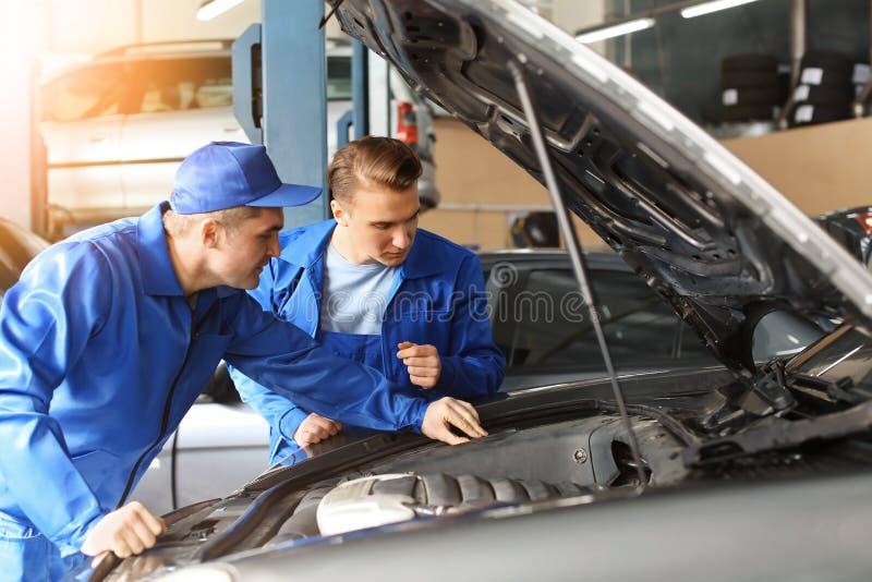 Meccanici maschii che riparano automobile nel centro di servizio immagini stock libere da diritti
