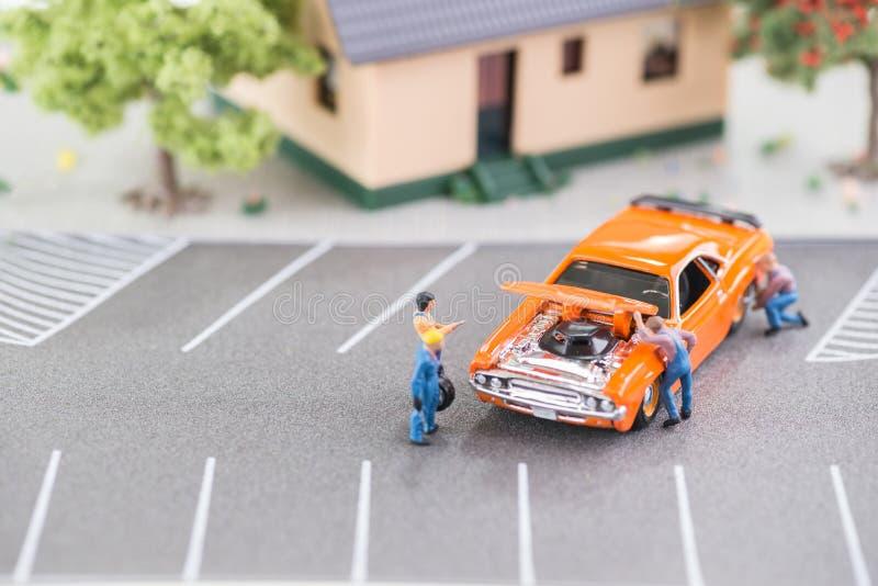 Meccanici miniatura che lavorano ad un automobile