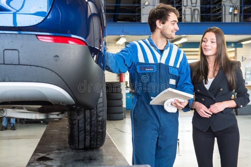 Meccanico amichevole, mostrante ad un servizio di assistenza al cliente il suo lavoro immagini stock