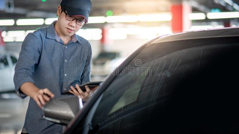 Meccanico asiatico che controlla lo specchietto retrovisore esterno dell'automobile fotografia stock