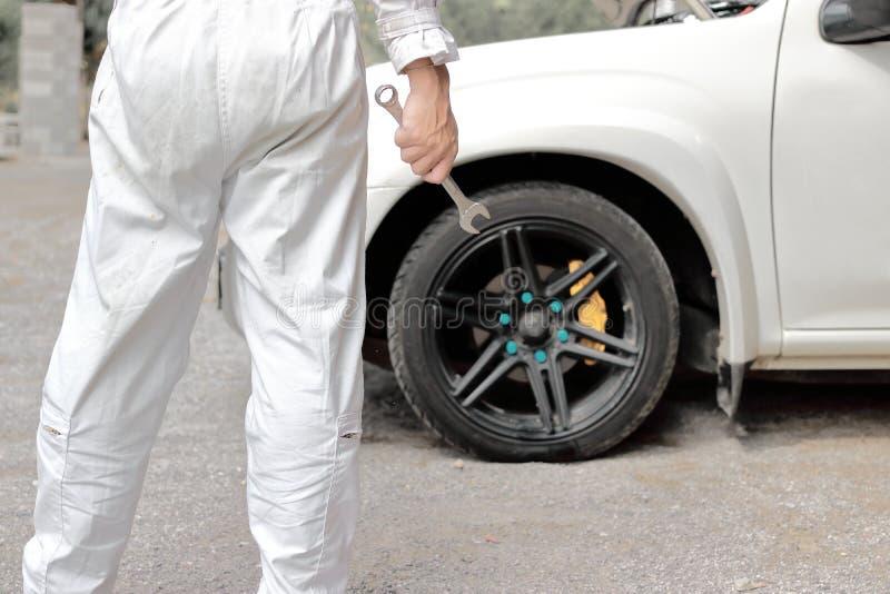 Meccanico automobilistico sicuro in chiave uniforme della tenuta in sue mani pronte a riparare il motore di automobile fotografie stock libere da diritti