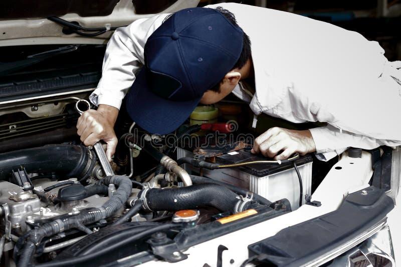Meccanico automobilistico in uniforme con la chiave che diagnostica motore sotto il cappuccio dell'automobile al garage di ripara fotografia stock