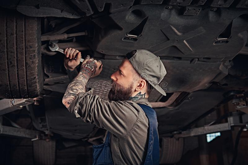 Meccanico barbuto in una riparazione uniforme la sospensione del ` s dell'automobile con una chiave mentre stando sotto l'automob fotografia stock libera da diritti