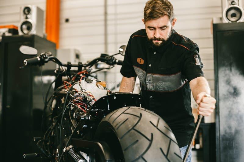 Meccanico bello che cambia la ruota del motociclo con gli utensili speciali fotografia stock libera da diritti