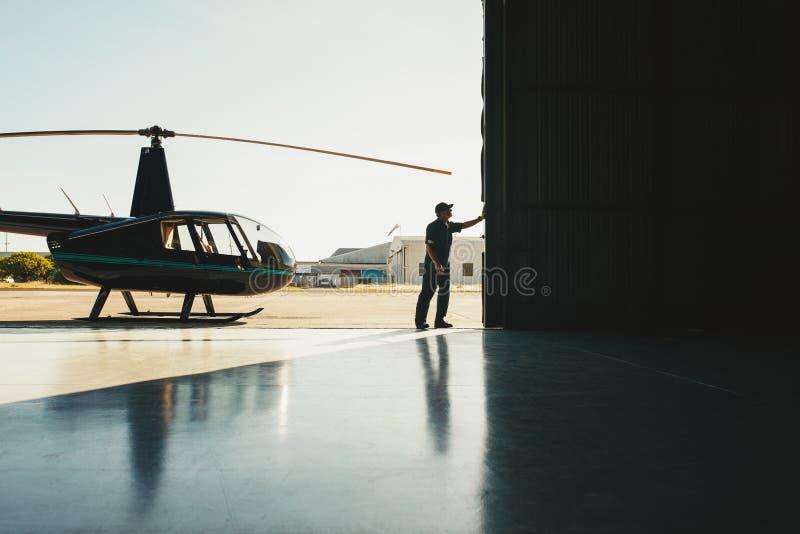 Meccanico che apre la porta di un'aviorimessa fotografie stock