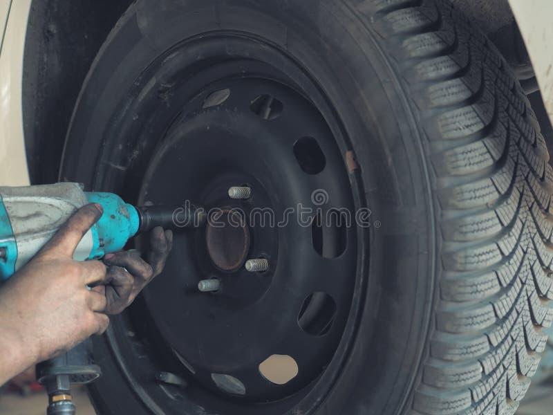 Meccanico che cambia una gomma di automobile in un'officina su un veicolo su una gru facendo uso di un trapano elettrico per alle fotografia stock libera da diritti